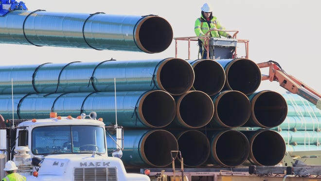Workers unload pipes for the proposed Dakota Access oil pipeline Saturday, May 9, 2015, at a staging area in Worthing, S.D. The pipeline would stretch from the Bakken oil fields in North Dakota to Patoka, Ill.