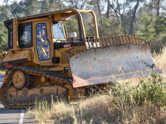 A Cal Fire bulldozer heads toward the fire off Texas