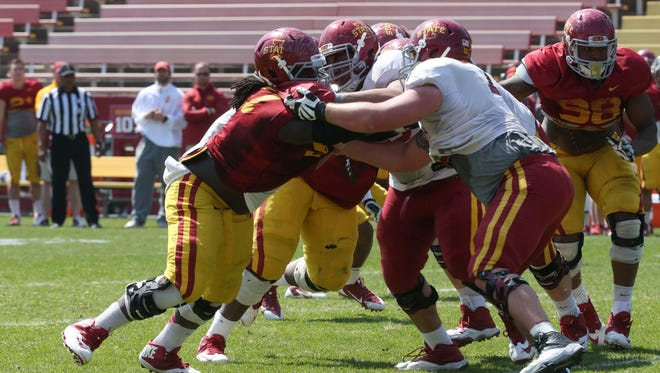 Defensive tackle Demond Tucker, left, tries to make a stop during the annual Iowa State spring football game on Saturday, April 11, 2015 at Jack Trice Stadium.