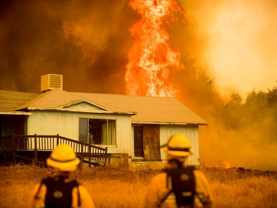 Flames rise behind a vacant house as firefighters work