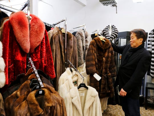 In this photo taken Friday, March 16, 2018, Benjamin Lin holds up a fur coat at the B.B. Hawk showroom in San Francisco. San Francisco could become the largest U.S. city to ban the sale of fur items, a move that would hearten animal lovers but frustrate niche business owners who say they're fed up with a city that dictates what retailers can or can't sell.