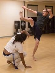Reporter Tad Mast performs a Meia Lau de frente over Capoeira instructor James Green III. The kick is part of a much longer dance utilizing the basics of capoeira strikes and defensive movements.