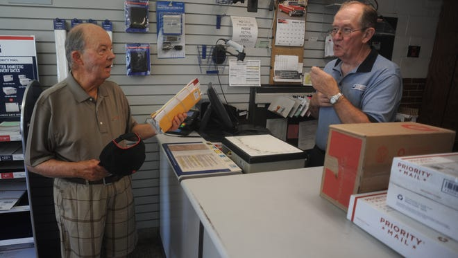 David Mingin, right, helps costumer James Dubell during his last week as a U.S. Postal Service clerk after 46 years.