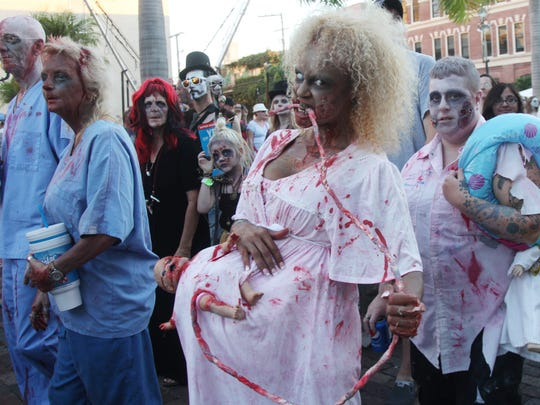 Zombies walk the streets of downtown Fort Myers while participating in the Zombie Walk during Zombicon 2014.