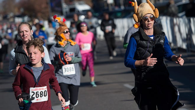 Runners sprint to the finish line during the 23rd Annual Thanksgiving Day Run on College Avenue Thursday, November 24, 2016. Over 4,000 people participated in the event.