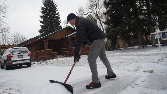 Jon Geller works to clear his driveway of snow at his home near City Park in Fort Collins on Thursday, December 21, 2017.