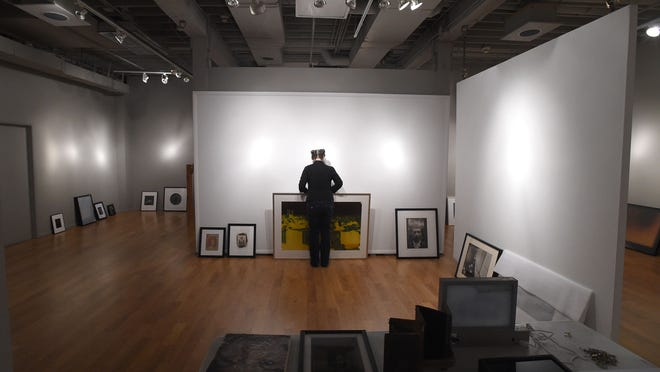 Director, Hammidah Glasgow, places a photo on the floor where is will be hanged at the Center for Fine Art Photography Monday Sept. 29, 2014.