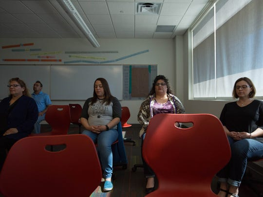Amy Himelright, right, leads a group of Las Cruces Public Schools food services employees in a mindfulness meditation exercise on Friday, March 2 at Centennial High School.