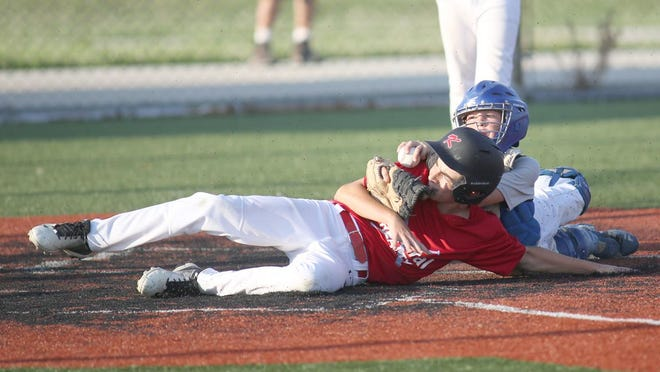 Huebert Fiberboard catcher Reece Townlain applies the tag on Central Realty's Cash Leonard in the second inning Monday night in Cal Ripken Major at the high school ballfield.