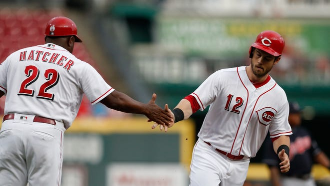 Cincinnati Reds' Preston Tucker (12) is congratulated on a two-run home run off Cleveland Indians starting pitcher Shane Bieber by third base coach Billy Hatcher (22) during the first inning of a baseball game Wednesday, Aug. 15, 2018, in Cincinnati.