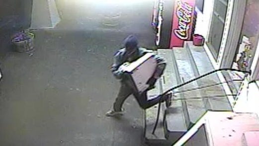 This Saturday, June 3, 2017 photo, shows a suspect leaving Gumboro Liquors with what state police said was a cash register. The suspect took the register when clerks at the store refused to hand over cash, said Delaware State Police.