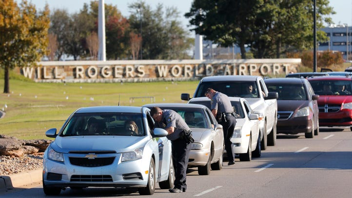 Oklahoma City police officers gather information from vehicles leaving Will Rogers World Airport, Tuesday, Nov. 15 2016, in Oklahoma City.