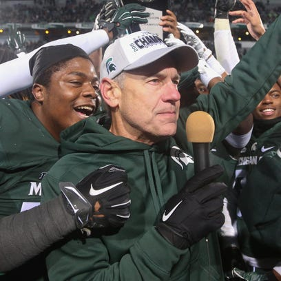 Michigan State coach Mark Dantonio talks to fans after