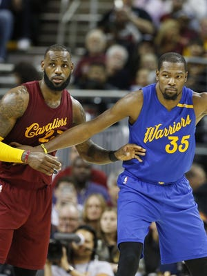 Golden State Warriors forward Kevin Durant (35) defended by Cleveland Cavaliers forward LeBron James (23) at Quicken Loans Arena.