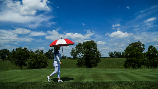 Golfer Brittany Lincicome carries an umbrella to shade herself from the sun Wednesday afternoon at Keen Trace Golf Course in Nicholasville before Thursday's start of the Barbasol Championship. She may need it for this weekend as rain is expected Friday through Sunday.
