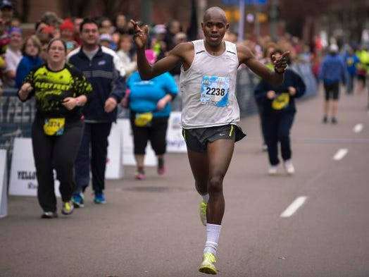 "Kiplangat ""Kip"" Tisia of Rochester completes his first place finish in the half marathon."