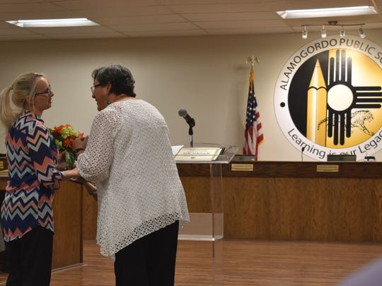 Kendra Lemke is given flowers and a Certificate of Recognition for Extraordinary Personal Action during the APS Board of Education meeting.