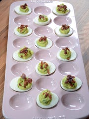 Avocado deviled eggs are topped with pancetta bits.