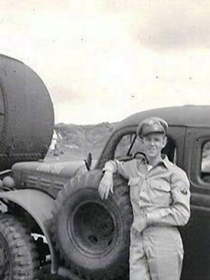 Dennis Schone leans against an Army vehicle at General MacArthur's Headquarter's Company in Brisbane, Australia - circa 1943.