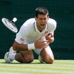 Novak Djokovic shouts in pain after falling onto the court during Friday's Wimbledon men's singles match against Gilles Simon on Friday in London.