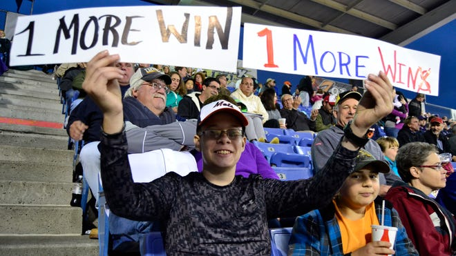 "Eric Brom, an eighth-grader at Chenango Valley, held a sign reading, ""1 more win,"" while watching the B-Mets game Friday night."