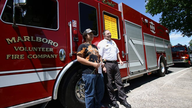 """2020 Marlington graduate Kyle Hostetler, left, poses with Marlboro Township Volunteer Fire Department Chief Matt Anstine in front of the department truck nicknamed """"the Duke."""" The stop was one of 38 the department made Sunday at Marlington High School graduates' homes. The visits followed an event at the high school at which the graduates received their diplomas. During the firefighters' visit, graduates were presented with a flower and a note of congratulations."""