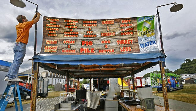 Paul Carson of Maine sets up his food stand on the midway for the Marshfield Fair's opening in 2017. Greg Derr/The Patriot Ledger