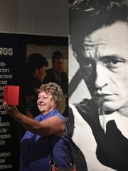 Shannon Walker takes a selfie of herself with a poster of Johnny Cash at the Country Music Hall of Fame and Museum Wednesday Aug. 9, 2017, in Nashville.