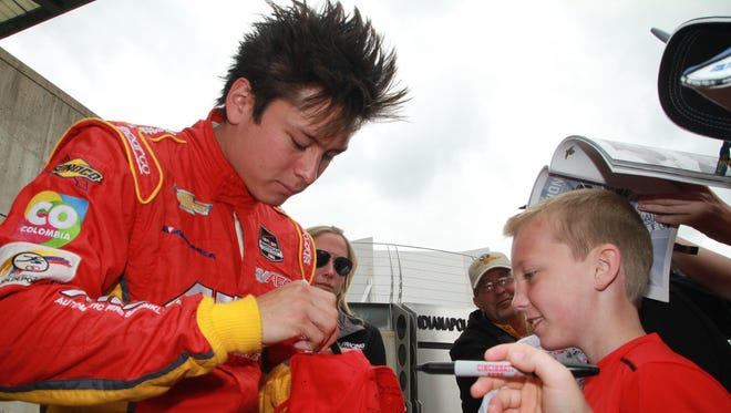 Driver Sebastian Saavedra, signs an autograph for Austin Britt, 9 from Greenwood, after qualifying at the Indianapolis Motor Speedway, May 17, 2014.