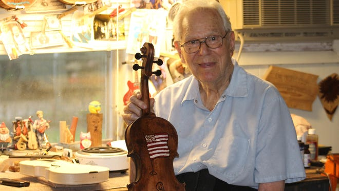 Hilton Lytle with one of his handmade fiddles. Lytle, 94, estimates he has made upwards of 670 fiddles in his lifetime.