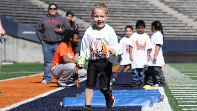 A participant in UTEP football kids' day participates in drills Saturday at the Sun Bowl.