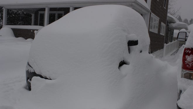 A car is buried Wednesday on Vermont Avenue in Binghamton.