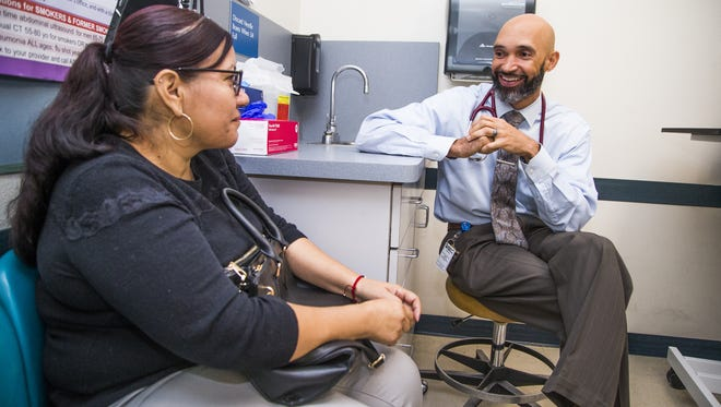 Patient Maria Gamez and Dr. Maurice Lee talk at the St. Vincent de Paul medical clinic in Phoenix.
