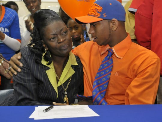 2-3-11, 1C  Pine Forest High School Football standout Louchiez Purifoy, right, comforts his mother Rena' Floyd, left, after he signed to play football with at the University of Florida next season.
