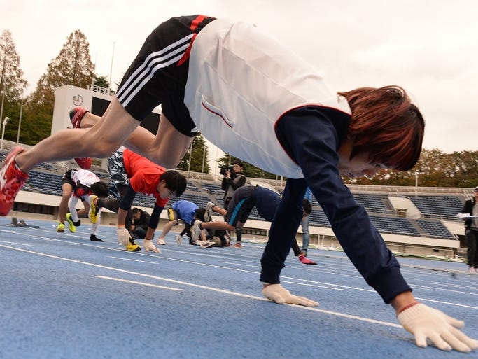 Kenichi Ito, the fastest man on all four limbs, warms up during the practice session before the quadrupedal 100-meter dash as he attempts to break his own Guinness world record on Nov. 14 in Tokyo.