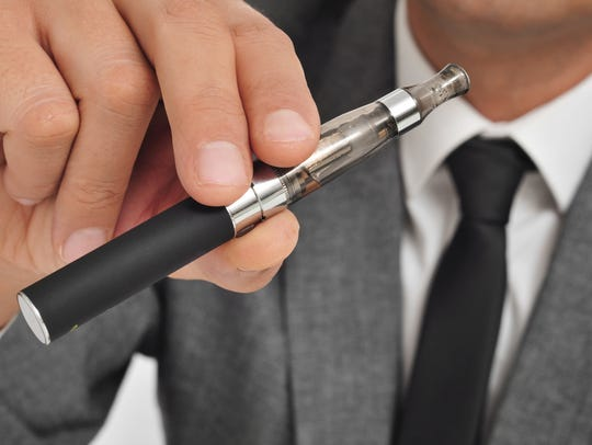A man holds an electronic cigarette.