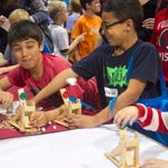 Roman Prashad, 9, left, launches marshmallows with his friend Skylar Dimoff, 10, and brother Julian, right, at the STEMtastic Day of Discovery at Harborside Event Center in Fort Myers on Saturday.