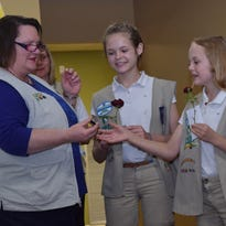 Girl Scout Troop 3428  leader Shannon Shelby (right) presents Maya Shelby (left), 16, a sophomore at Tioga High School, a Gold Award for her project on building relationships with God and with each other. Maya painted stepping stones and a bench at her church.