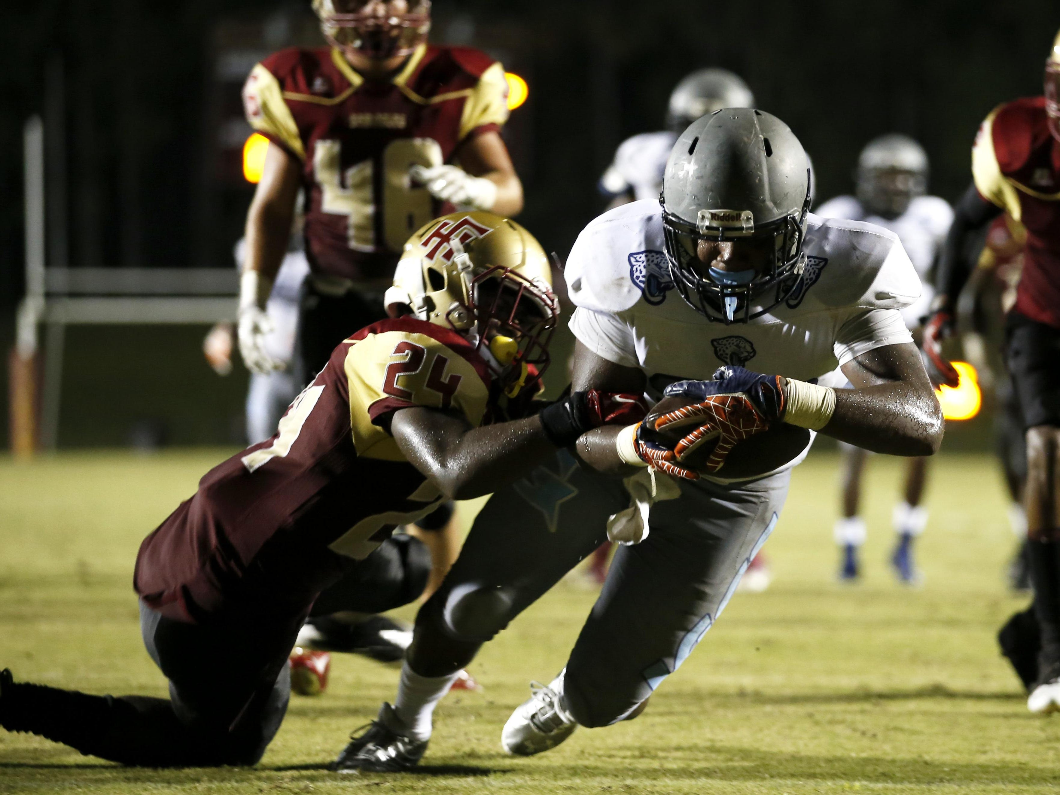 East Gadsden's DeShade Holton drags Florida High's Carlos Williams into the endzone for a touchdown during their game at Florida High on Friday.