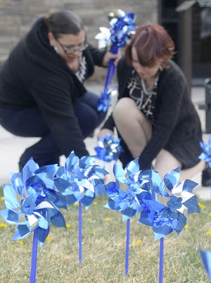 City employees Tina Rodriguez (left) and Amanda Perry place pinwheels in the lawn.