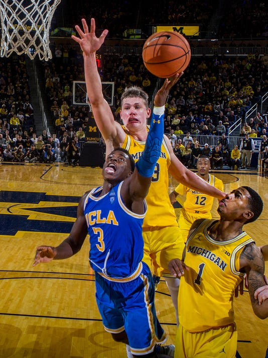 UCLA guard Aaron Holiday (3) attempts a basket, defended by Michigan forward Moritz Wagner, top, and guard Charles Matthews (1), in the second half of an NCAA college basketball game at Crisler Center in Ann Arbor, Mich., Saturday, Dec. 9, 2017. Michigan won 78-69 in overtime. (AP Photo/Tony Ding)