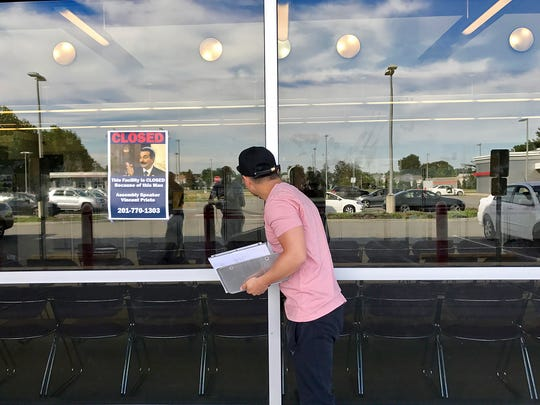 A New Jersey resident peers into the state Motor Vehicle Commission office in Lodi after finding out it is closed Monday due to the government shutdown. A flier blaming Assembly Speaker Vincent Prieto is seen taped to the window.