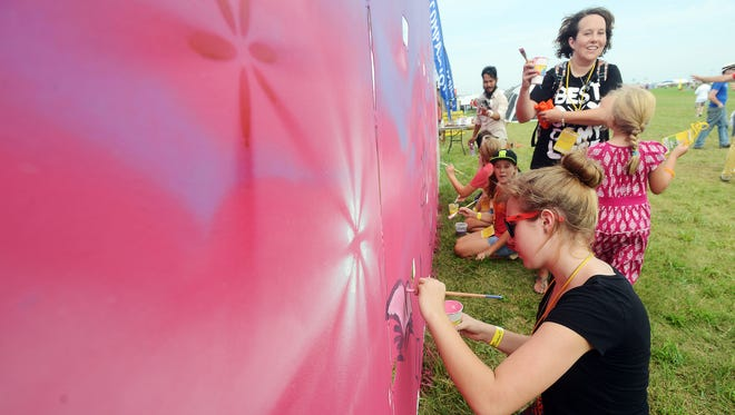 Kathryna VanDer Zwaag of Omaha paints a flower on a wall for Compassion International Saturday afternoon at LifeLight, Sept 5, 2015.