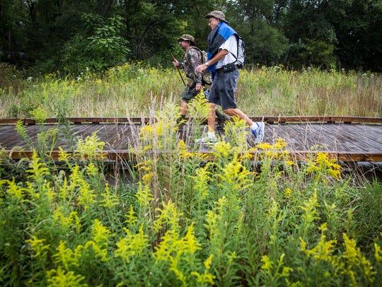 People walk through the John Craddock Wetland Nature