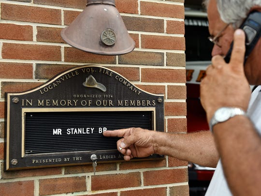 Loganville Volunteer Fire Company member Tom Frantz adds Stan Brown's name to a memorial plaque outside the fire hall Saturday, Aug. 12, 2017. Brown, the patriarch of the family-owned Brown's Orchards & Farm Market in Springfield Township, died of cancer at age 84 Saturday morning.