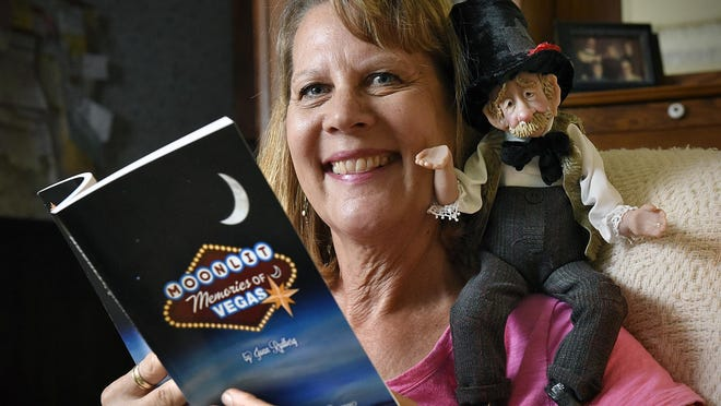 """Artist Joan Rydberg talks Thursday about starting a new adventure with her first book, """"Moonlit Memories of Vegas."""" The doll on her shoulder is one of her creations."""