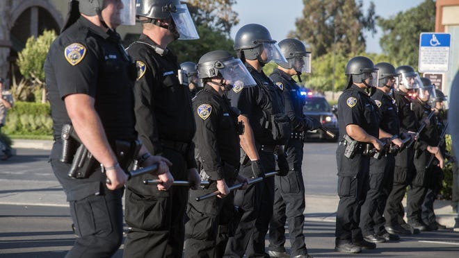 Stockton Police officers line up to block protesters progress on Pacific Avenue at Robinhood Drive in Stockton on June 5.