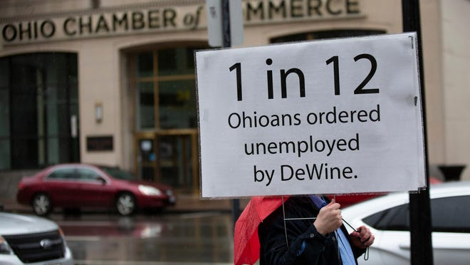 A protester holds a sign outside the Ohio Statehouse in April. An Ohio Realtors survey of 700 households shows the deep economic cost of the coronavirus pandemic.