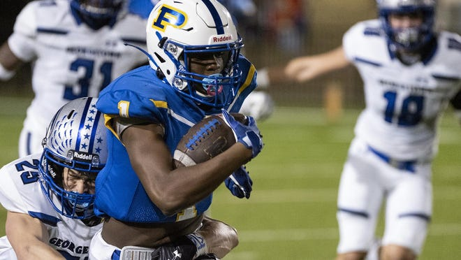 Pflugerville's Donald Springs makes a catch and turns up field as Georgetown's Adam O'Brien wraps him up during a high school football game at The Pfield on Friday.