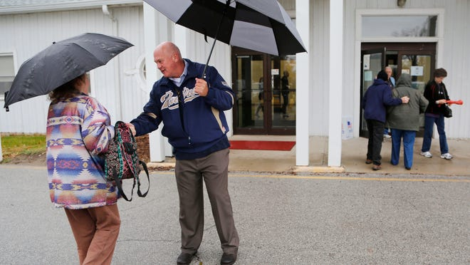 A steady rain falls as candidate for Sheriff Barry Richard greets voters Tuesday, November 4, 2014, at the Tippecanoe County Fairgrounds in Lafayette.